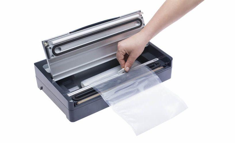 Prikaz rezanja folije na srebrno-sivom aparatu za vakumiranje SV2000 s ugrađenim nožem.