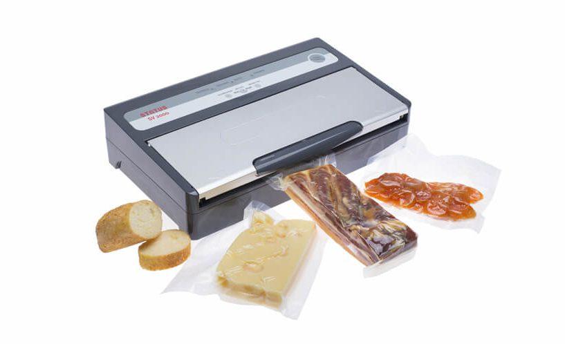 Srebrno-sivi aparat za vakumiranje SV2000: vakumiranje slanine i sira.