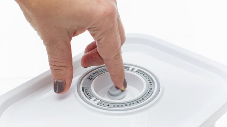Roka na belem pokrovu Statusove steklene vakuumske posode, krožni koledar.