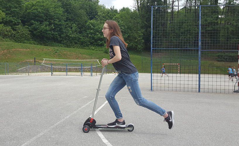 Dekle na igrišču se vozi s skirojem.