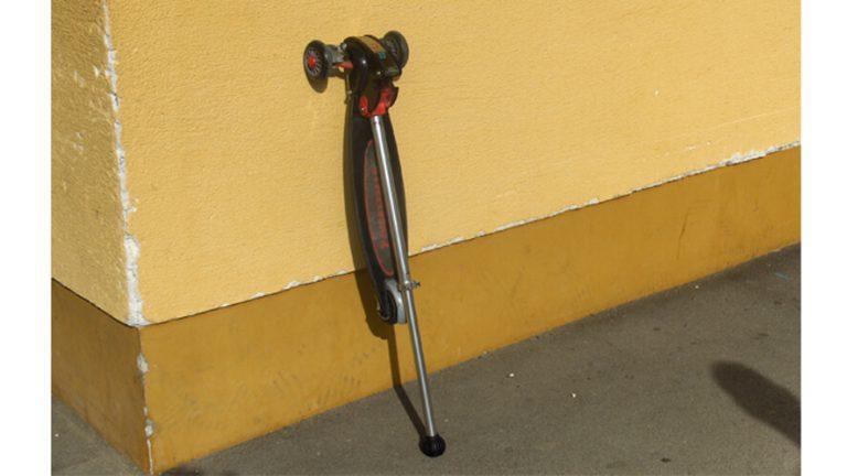 Zložen skiro Streetboard prislonjen na zid.