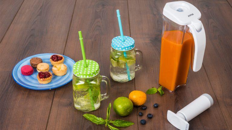 Vakuumski vrč Status s sokom, dva kozarca limonade in prigrizek na temnem rjavem lesu.